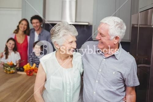 Happy grandparents with family in kitchen