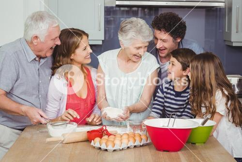Smiling grandmother cooking food with family