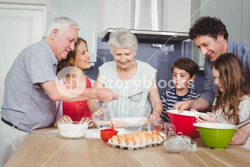Smiling family preparing food in kitchen