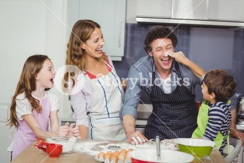 Happy family enjoying while cooking food