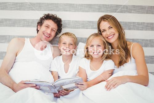 Portrait of smiling family on bed