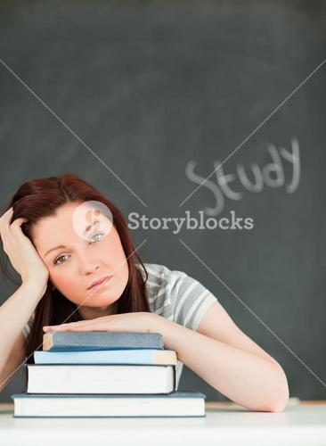 Potrait of a tired young woman studying