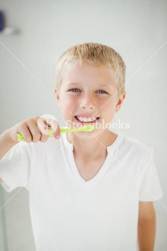 Portrait of boy smiling while brushing teeth