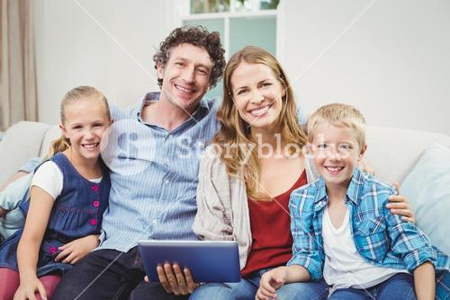 Happy family sitting on sofa in living room