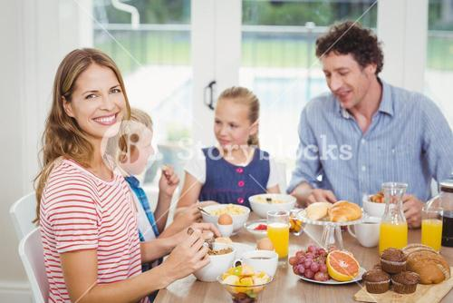 Happy mother having breakfast with family at table