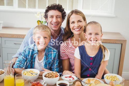 Cheerful children and parents having breakfast by table