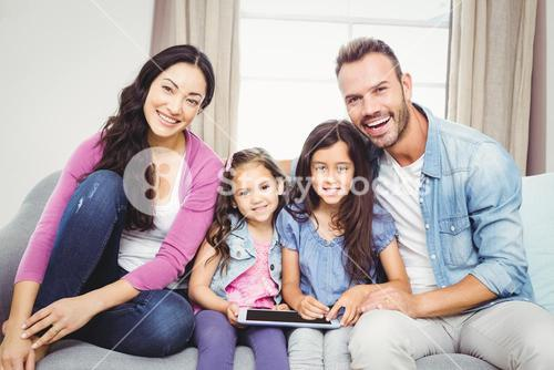 Family with tablet computer sitting on sofa