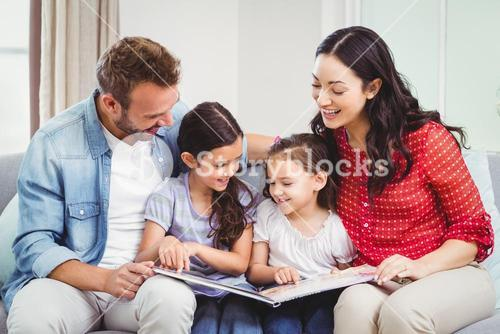 Parents looking in picture book while sitting with daughters