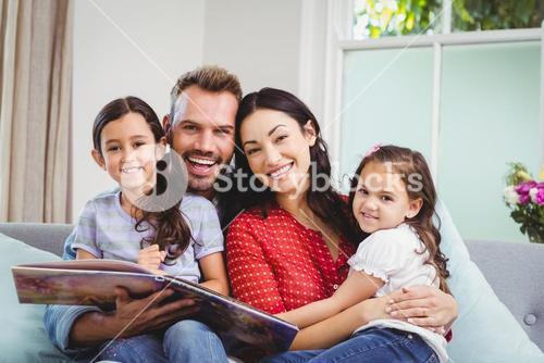 Portrait of happy family with picture book on sofa