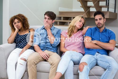 Upset young friends on sofa in living room