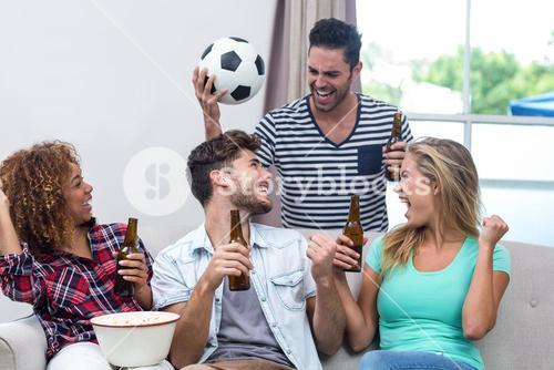 Friends enjoying beer while watching soccer match