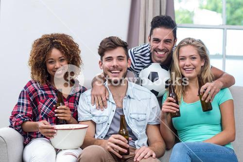 Multi-ethnic friends enjoying beer while watching soccer match