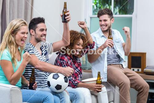 Multi-ethnic friends with beer bottle enjoying soccer match