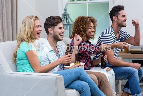 Cheerful multi-ethnic friends enjoying soccer match at home
