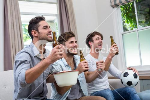 Male friends enjoying beer while watching soccer match on TV