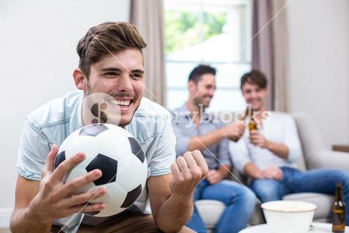 Young man watching soccer match while friends in background