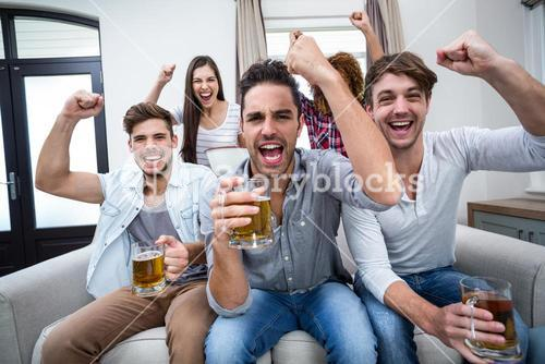 Friends cheering and drinking alcohol while watching soccer match