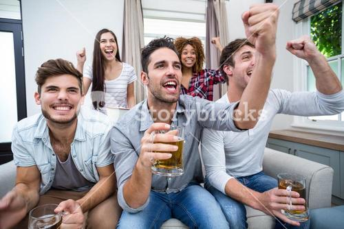 Friends cheering while watching soccer match on TV
