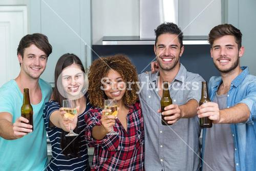 Portrait of multi-ethnic friends showing beer and wine