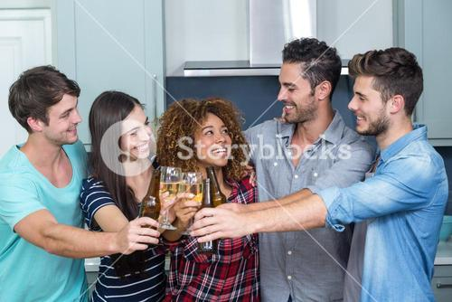 Multi-ethnic friends toasting beer and wine in kitchen