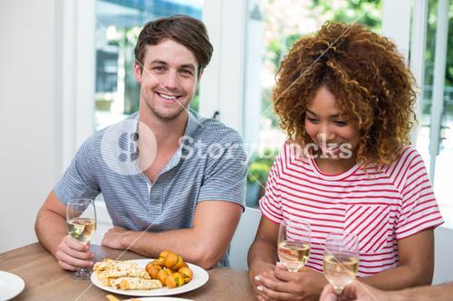 Young friends with wine and food on table