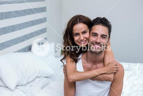 Wife embracing husband on bed at home