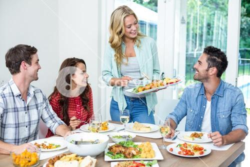 Woman serving food to friends