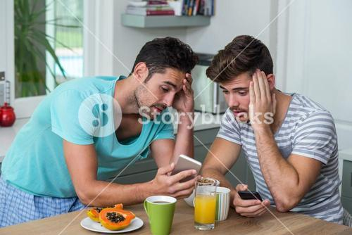 Frustrated male friends using phone