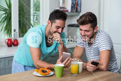 Smiling male friends using phone