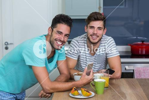 Portrait of male friends using phone