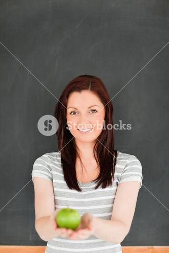 Portrait of a cute redhead against a blackboard
