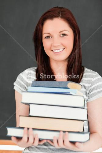 Portrait of a smiling redhead holding books