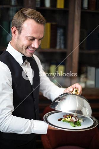 Handsome waiter serving meal
