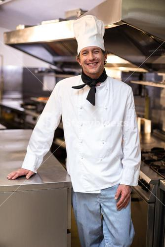 Handsome chef leaning on counter