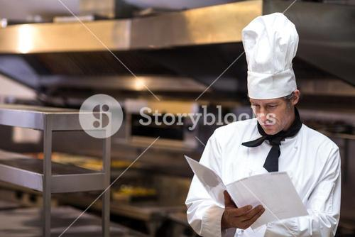 Handsome chef reading menu