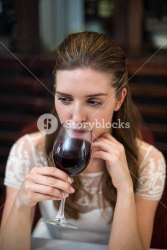 High angle view of happy woman drinking wine glass