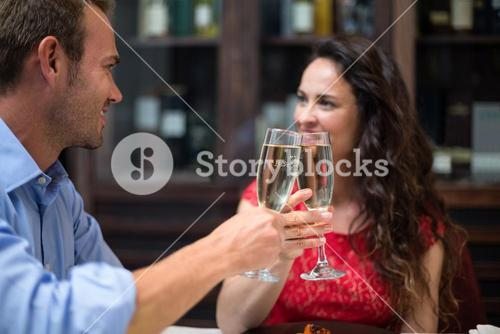 Cheerful couple toasting champagne flutes