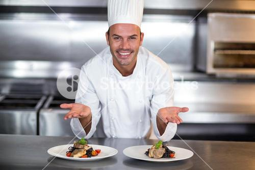 Portrait of smiling chef showing food plates in kitchen