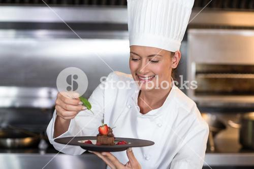 Smiling female chef holding plate of food in kitchen