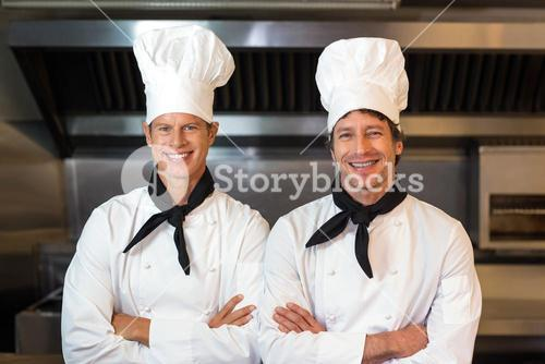 Portrait of smiling male chefs in kitchen