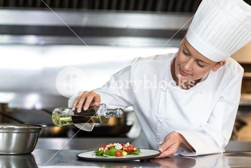 Female chef pouring oil on food in plate