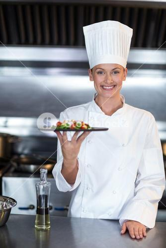 Portrait of smiling female chef holding food plate