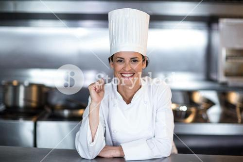 Portrait of smiling female chef in kitchen