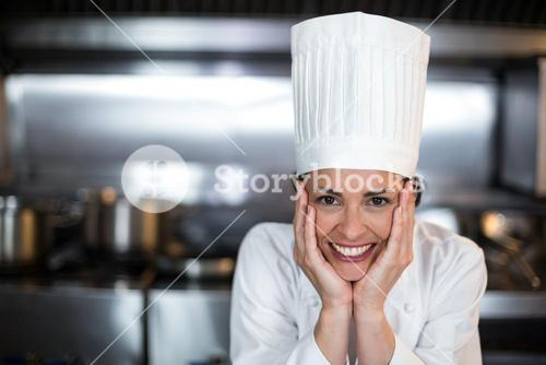 Portrait of beautiful female chef in kitchen