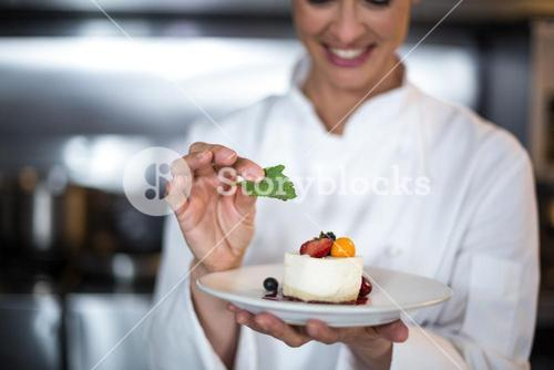 Smiling female chef holding food plate in kitchen
