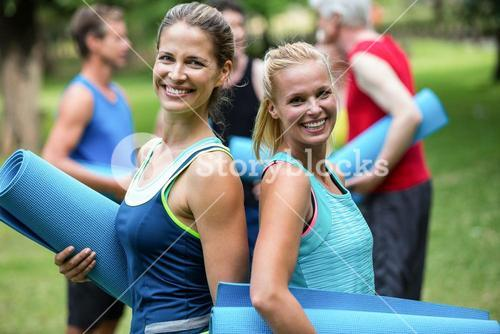 Fit women posing with sports mats back to back