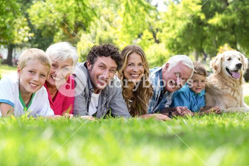 Family with dog lying on the grass in the park