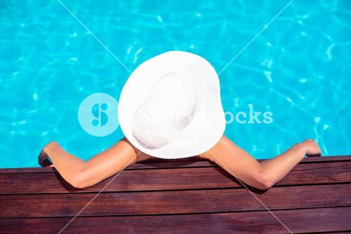 Woman wearing hat leaning on wooden deck by poolside