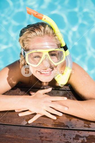 Happy woman with snorkel gear leaning on pool side