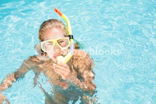 Portrait of woman with snorkel gear swimming in pool